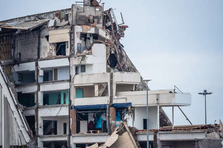 Destroyed building on the background of the sky. Wall of a demolished house. Old building during demolition. Demolition services. Concept - organization of the demolition of multi-storey buildings