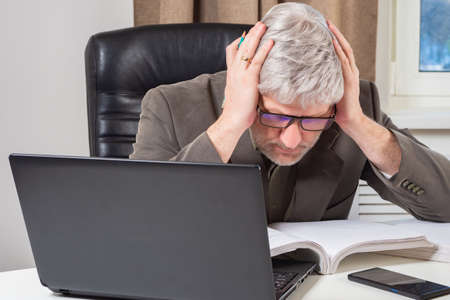 Accountant man holding his head. Concept - he's worried about something. Accountant man while working with documents. Gray-haired auditor at his desk. Laptop next to auditor. Accountant career.