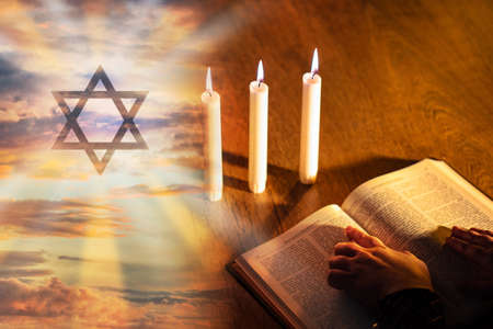 Study of Judaism concept. Jewish religion. Judaism logo next to bible. Reading Jewish writers. Burning candles next to prayer. Jew is reading a book. Judaism as a symbol of Jewish religion.