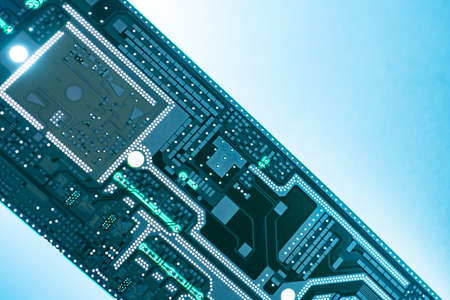 PCB board on a blue background. Blank PCB board close-up. Creation of computer boards. Template for PCB board manufacturing. Microcircuit without copper elements. Design concept microcircuits Reklamní fotografie