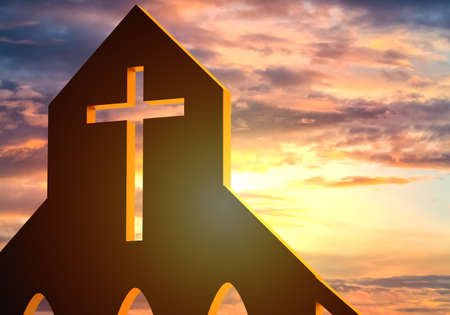 Fragment of a building with a Catholic cross. Catholic cross on a sunset background. Hole with a Christian cross in building. Building for prayer of Christians. Concept - religious shrines. Stockfoto