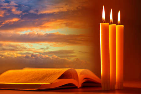 Candles and an open book as a symbol of religion. holy book on background of morning sky. Reading holy book. Concept - study of Bible or Koran. Reading religious literature. Opened Religious Textbook Stockfoto