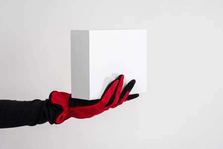 Delivery of goods from online stores. Home delivery. A hand in a work glove holds a white box. Delivery of purchases. Courier service. Courier business. Warehouse, parcels, logistics. Stockfoto