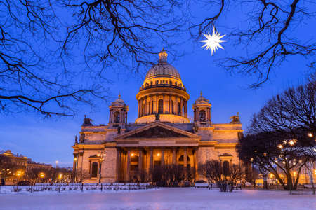 Winter evening in Saint-Petersburg. New Year in Russia. St. Isaac Cathedral at Christmas. St. Isaac Cathedral on the background of decorative luminous star. Winter trip to Russia. Russian architecture