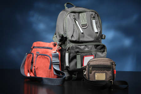 Bags of different types and sizes stand side by side. Urban backpack next to small bags. Three bags are on table. Concept - shop of handbag and backpacks. Sale of modern urban backpacks. Stockfoto