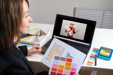 Remote conversation between architect and designer via laptop. Architect talks with construction foreman via video link. Architect makes a video call to builder. Portrait of a woman designer at work