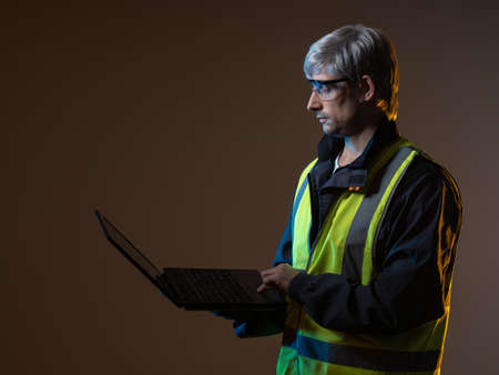 Portrait of a working engineer with a laptop. Working engineer in a yellow vest. A mature engineer is holding a computer. Ð¡oncept - worker of an engineering company. Engineering bureau employee