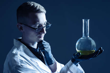 Pensive laboratory assistant on a dark blue background. Man in lab technician robe pondered. He examines a large flask. A portrait of a researcher in a white coat. Young scientist lab assistant