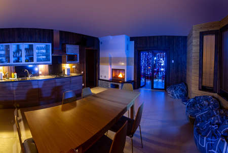 home interior kitchen. Large wooden table is located in kitchen. Evening interior with neon lighting. Dining room with fireplace. Rest room is combined with kitchen. Fireplace in lounge.