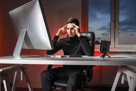 Office worker in a pensive pose. He pretends to look thoughtful. Businessman in his own office. Man looks at the monitor with a pensive look. Office worker looks at computer screen.