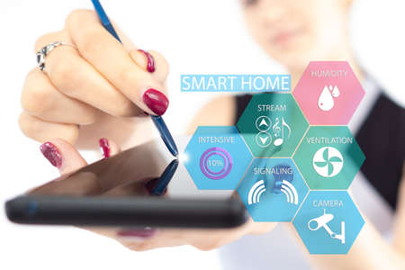 IOT concept. College of business woman with smartphone and smart home symbols. It controls smart home technology. Woman manages IOT technology. She holds out a smartphone with IOT icon Foto de archivo