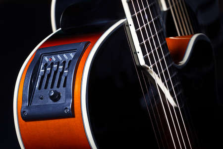 Timbre block on an acoustic guitar. Acoustic guitar timbre block close-up. Fragment of a guitar with modern timbre blocks. Concept - sale of spare parts for musical instruments. Dark background Stockfoto