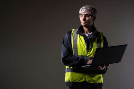 Man in yellow vest holds a laptop. Concept - he's a computer scientist in a industrial factory. Career as computer technician in industrial enterprise. Male geek on a dark background. Gray-haired geek Foto de archivo