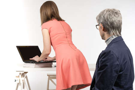 Harassment at work. Young woman at table feels that she is being watched. Gray-haired man is watching a colleague girl. Concept - man looks at ass with his submissive. Harassment towards employees