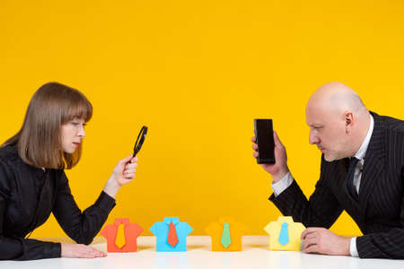 Staffing services concept. Man and woman are engaged in selection employees. Rendering to staffing services. Recruiters test potential employees. Rukruters on a yellow background. Man made of paper