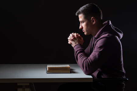 Christian prayer. Man praying before bible. Guy crossed his palms for prayer. He holds his hands over Bible. Young guy praying over black background. He reads Christian Bible. Religious rites