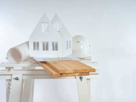 Architect's desktop. Carpenter table on a white background. Layout of cottage and architect's helmet. Wooden planks on carpenter table. Builder workplace. Beams as a symbol of wood construction