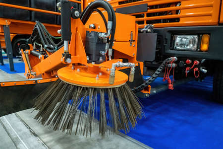 Special equipment for street cleaning. Sweeping brush - cleaning machine close-up. Fragment of a street sweeping machine. Service car for street cleaning. Sweeping machine inside hangar