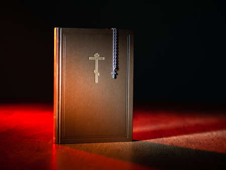 Bible icon on leather book. Bible with a picture of Catholic cross. Concept - study of religious literature. Catholic book on a wooden table. Orthodox cross hanging on bible. Book religious christian