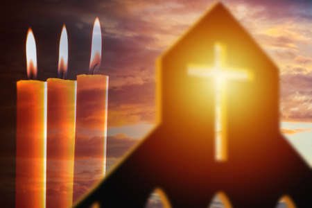 Three church candles. Church candles next to Christian cross. Symbols of Christian faith. Church candles on a sunset background. Concept - Catholicism. Articles of Faith in Jesus Christ.