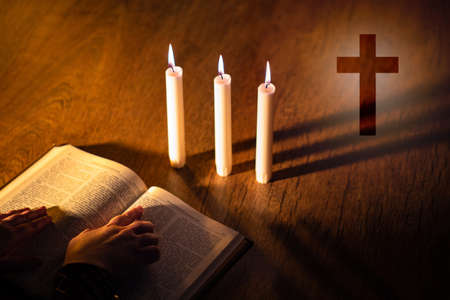 Priest hands on bible. Burning candles next to Christian cross. Cross symbolizes Catholicism or Orthodox. Attributes of Christianity on a wooden table. Catholic prays to God. Orthodox studying bible Stockfoto