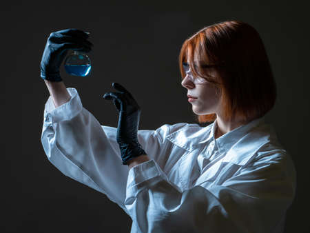 Biological laboratory worker woman. She studies various bacteria. Woman laboratory assistant on a dark background. Lab assistant examines a test tube with some substance. Biologist on dark background Foto de archivo