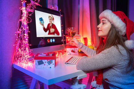 Virtual communication on Christmas. Girl in santa hat speaks video chat. She is holding wine in her hands. Virtual communication in new year due to quarantine. Christmas ones during a pandemic