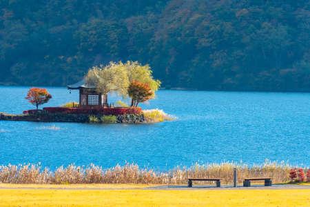 Gazebo in Lake Kawaguchiko. Arbor on island in Japan. Landscape of Japanese nature. Panorama of Lake Kawaguchiko. Japanese style gazebo on a tiny island. Japan bright autumn landscape