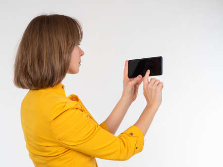 Girl in a yellow jacket holds a phone. She stands sideways to camera. Businesswoman with a smartphone on a white background. Concept - businesswoman demonstrates an apps on her phone. Business apps.