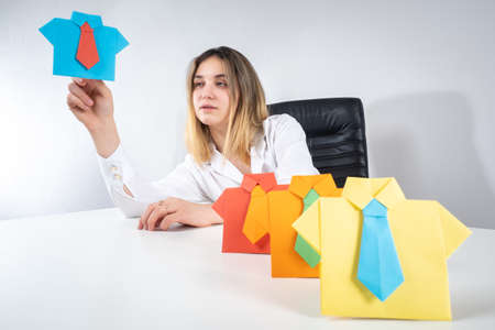 Recruiter at work. Paper person as a staff symbol. Woman recruiter selects a candidate for promotion. Girl makes a career as a recruiter. She selects employee for a vacant position Foto de archivo