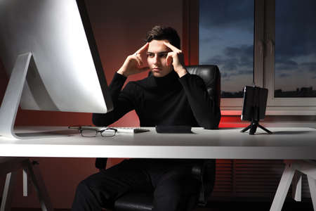 Office worker is thinking about something. Guy at working table is holding his head. Office worker is dressed in a casual style. He looks at monitor with a thoughtful look. Office worker is tense.
