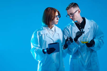 Medical researcher on blue background. Two medical researcher a test tube in hand. Young guy and a girl in uniform of doctors. Tablet computer in hands of researchers. Research in laboratory. Foto de archivo