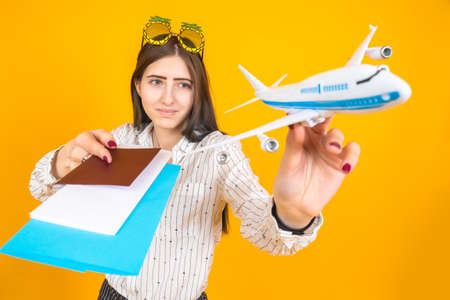 Woman traveler with displeasure looks at plane. She holds out a model airplane. Girl is unhappy with cancellation of flights. International flight cancel concept. Traveler documents to camera