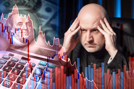 The man is trying to concentrate. Concept - a man is tired of the recession. Recession in the economy. The fall of financial buyers. The chart is decreasing. US dollars. Bad investment