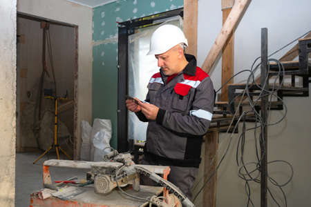 Builder changing blade on circular saw. He holds the circular saw blade in his hands. A man in a construction suit next to a stationary circular saw. Builder in the room being repaired