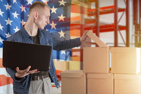 American business. American online shop. Warehouse in USA. E-business in America. Delivery from USA. Online business. Goods, parcels delivery. Warehouse worker with laptop.