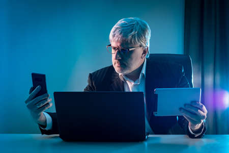 Gray-haired man with phone and tablet in his hands. Businessman with many gadgets. Concept modern businessman. Adult man at office table with laptop. He is holding a smartphone and a tablet computer