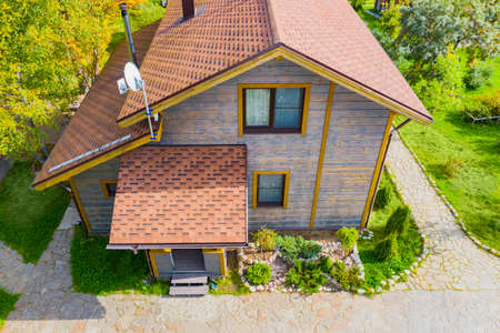 The house with a soft roof top view. Two-storey wooden cottage. A house with a TV antenna on the roof. Construction of houses. Landscape design. Stone paths and lawns around the house.