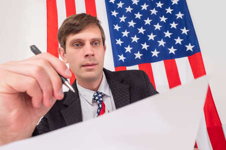 American holds a sheet of paper and a pen. American fills documentation. Concept - filling reports for government. USA resident fills a report on paper. America flag in background. Bureaucracy in USA