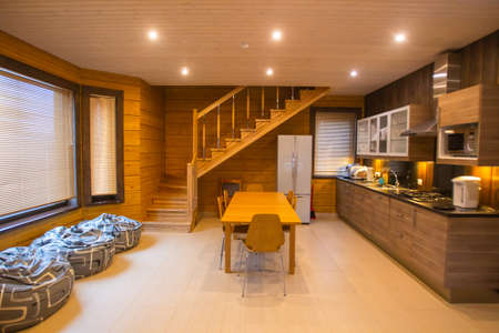 Living room interior. Country house kitchen interior. Kitchen is combined with dining room. Interior is made of light wood. Concept - renting a country house. Living room of country house. Foto de archivo