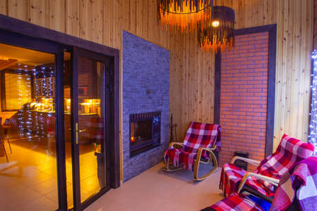 Interior of hotel. Lounge with fireplace. Small room in a country hotel. Several rocking chairs in a small room. Concept - rest in a country hotel. Glass door leading to dining room.