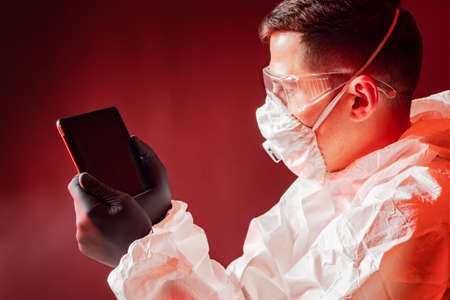 Man in a sanitary protection suit. He looks at tablet screen. Concept - epidemiologist is using some kind of application. Application to fight epidemic. Young man works as an epidemiologist. Foto de archivo
