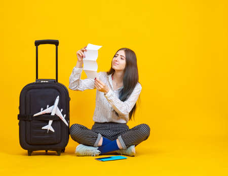 Traveler is holding a list of some kind. Airplane as a symbol of air travel. Travel suitcase next to traveler. Travel on a yellow background. Concept - business in field of air tourism.