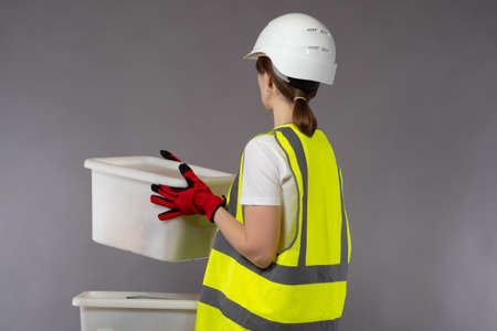 Warehouse worker woman. She is holding a plastic box in her hands. Warehouse worker with his back to camera. Boxes represent warehouse activities. Woman in a yellow vest and a helmet.