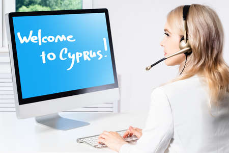 Tour to Cyprus Concept. Purchase a cruise to island of Cypriot. Buying a ticket to Cypriot Republic. Welcome to Cyprus inscription on computer screen. Girl operator sells tickets to Cyprus.
