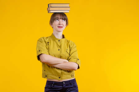 Young woman with books on her head. Student with textbooks on her head. Girl student on a yellow background. Portrait of student with books. Girl with textbooks crossed her arms. Concept buying books