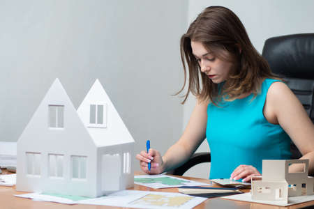 Architect next to the layout of the house. Concept - the workplace of the architect. Girl works with drawings at home. A woman with a marker makes notes in the drawings. Preparation for construction