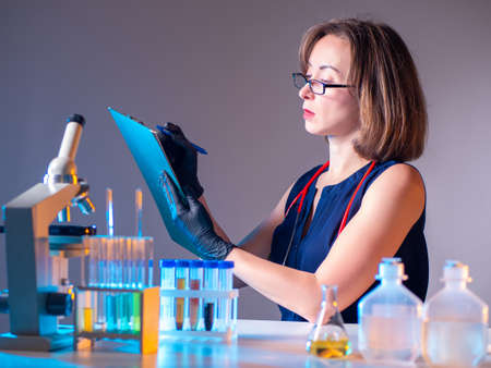 Doctor works in laboratory. She studying someone's tests. Concept of delivery of tests to clinics. Clinic doctor at work. Woman laboratory assistant is writing something down. She sits at lab table