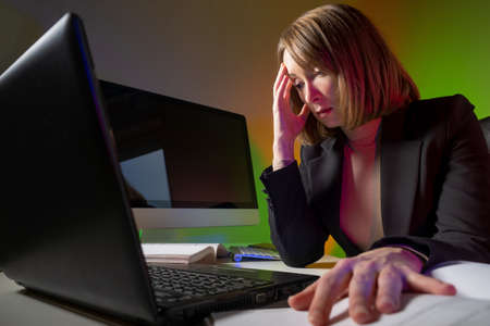 Tense businesswoman next to computer. Concept - she counts business income. Woman is studying accounting of the company. Accountant is working hard. Accountant holding his head while working