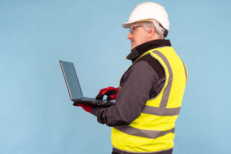 Construction planning contractor concept. Developer of building plans on a blue background. Planner engineer with a laptop in his hands. Builder Engineer working on laptop while standing. Foto de archivo